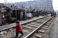Shenyang, China - March 11 2009: A child plays along a railway at a shanty town where residents will move into low-rent apartments provided by the government, CHINA, december 2009